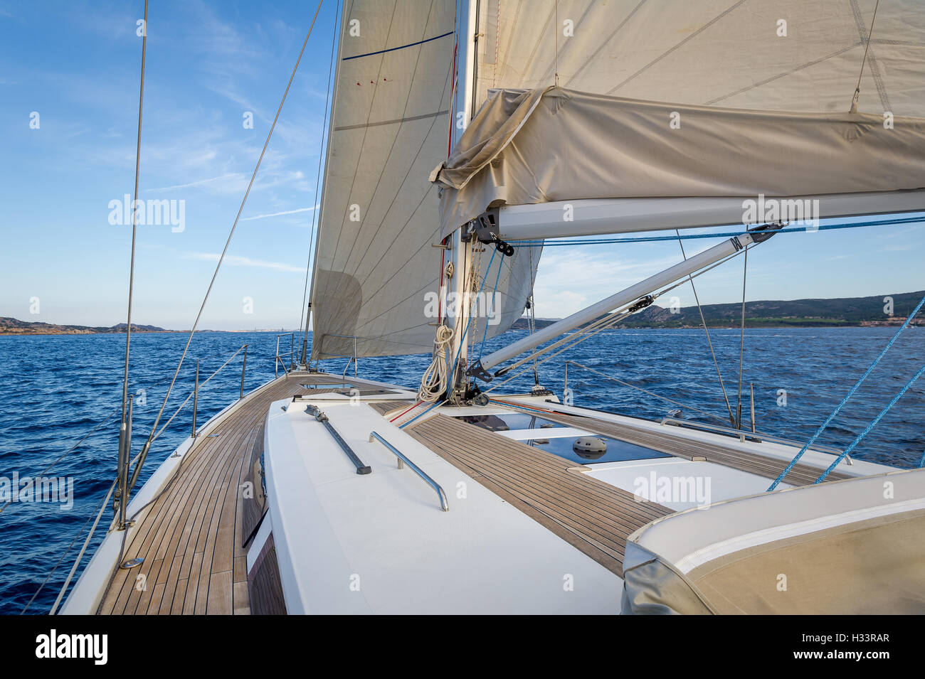 Sailing boat teak deck and hoisted sails, view from the cockpit to the bow. - Stock Image