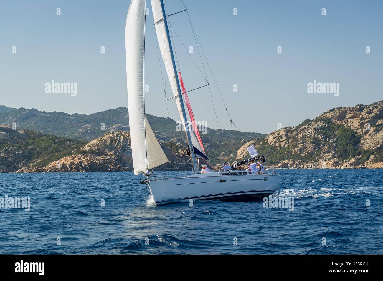 Cruising sailboat sailing near Sardinia island shores. - Stock Image