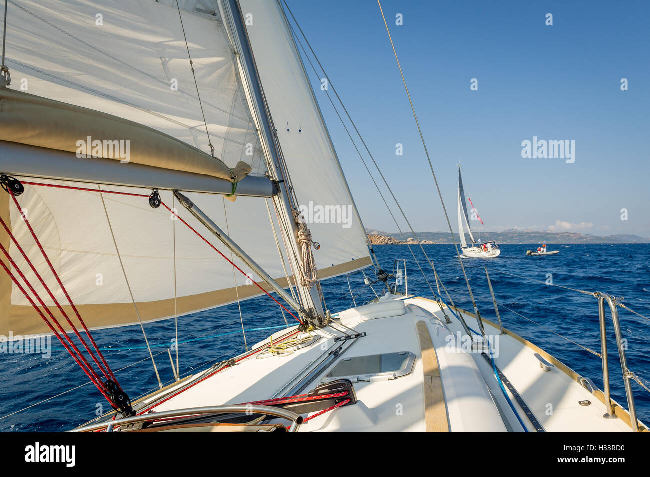 Sailing boat going fast on she's sails, view from the cockpit to bow. - Stock Image