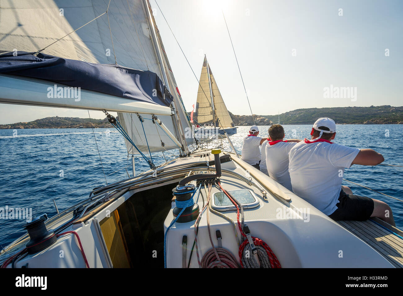 Onboard view of racing sailing yacht with a crew sitting on the starboard side - Stock Image