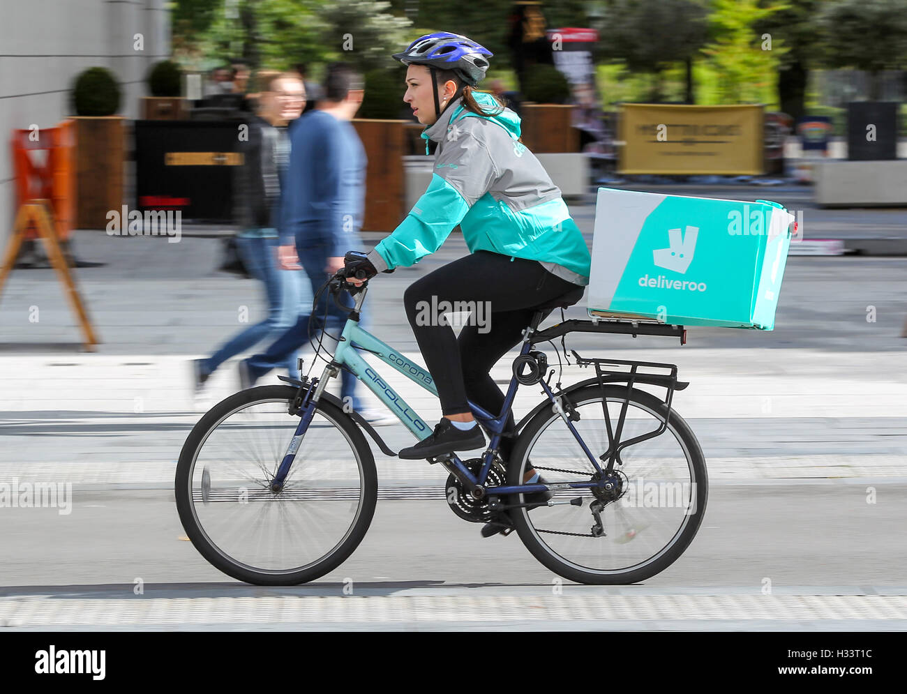 A female Deliveroo cyclist riding with a package on her bike - Stock Image
