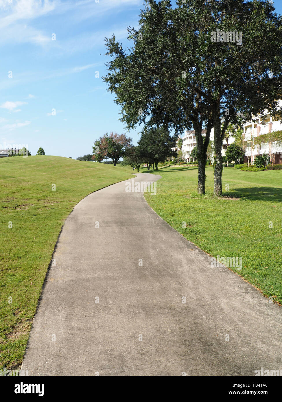 macadam path or walkway by a large grass area and trees - Stock Image
