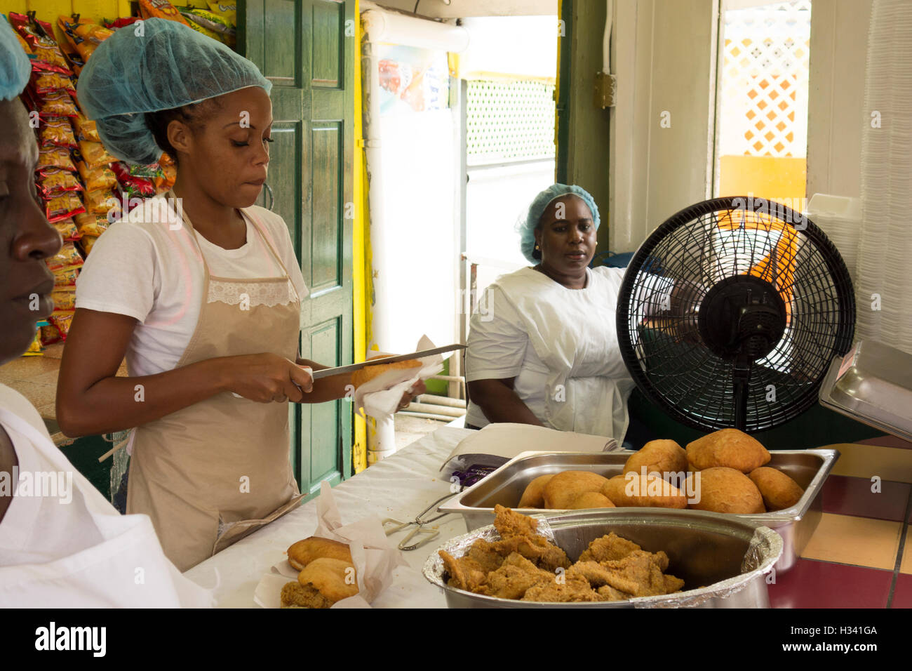 woman makes traditional Trinidad dish of Shark and Bake fish sandwich at food snack stall at Maracas Beach Trinidad - Stock Image