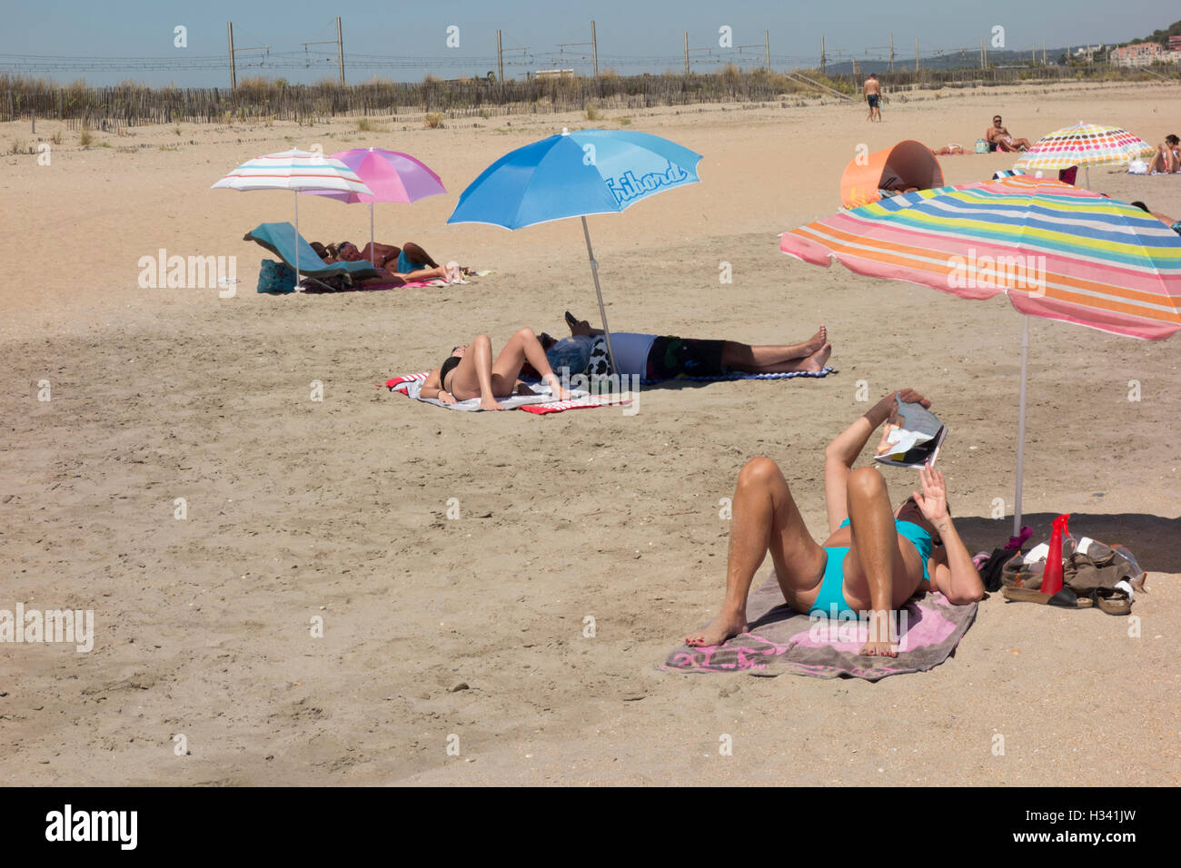sunbathers on sandy beach near Sete in Herault Languedoc Roussillon South of France - Stock Image