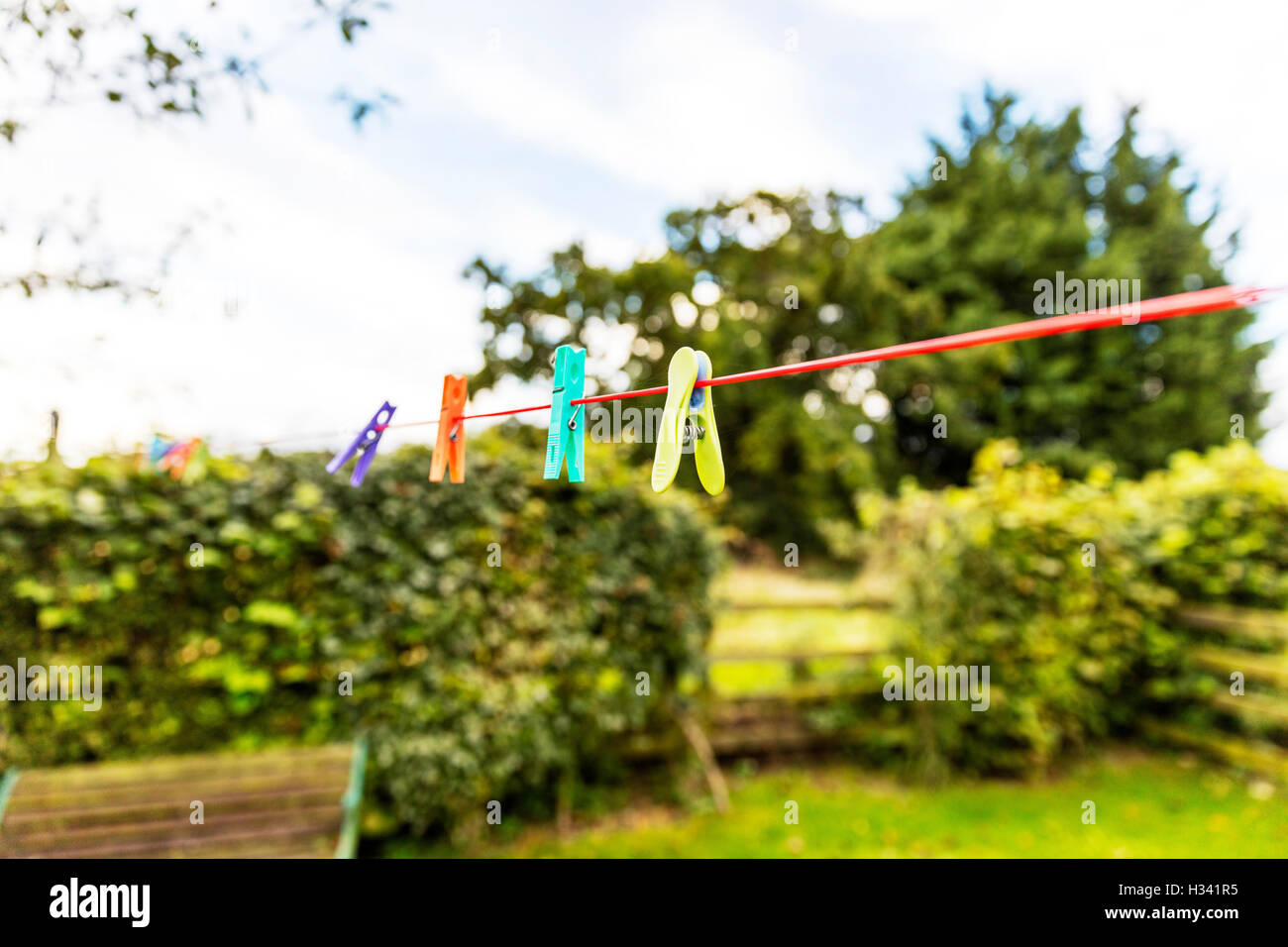 Clothes pegs on washing line clothes peg clipped to line outside garden UK England GB - Stock Image