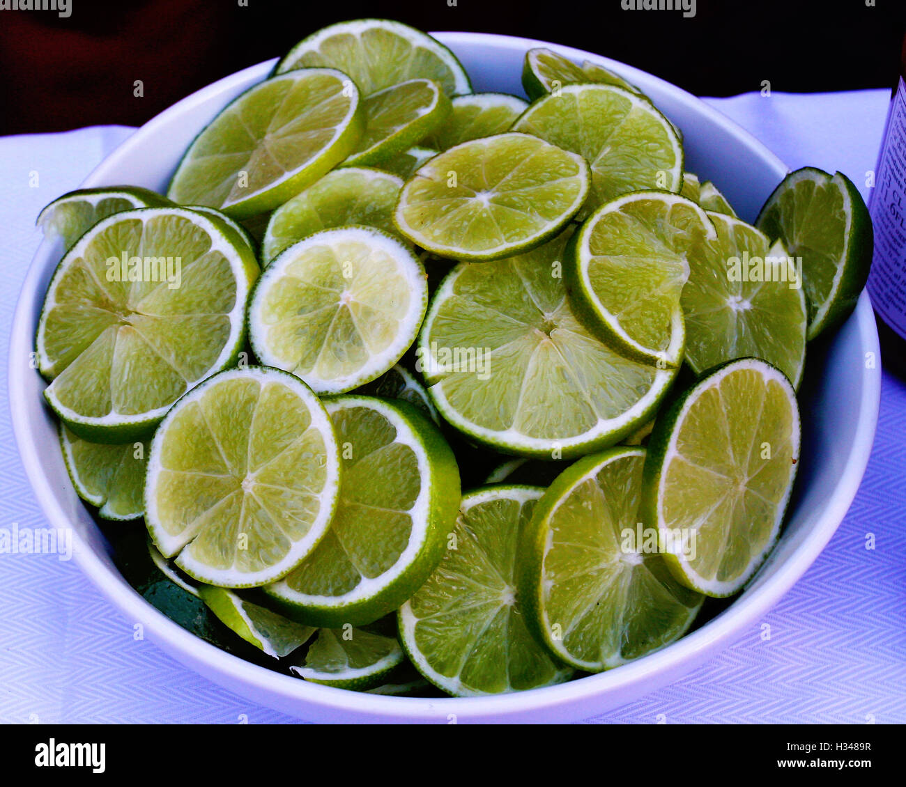Limes in a bowl. Sliced and ready for BBQ and cocktails - Stock Image