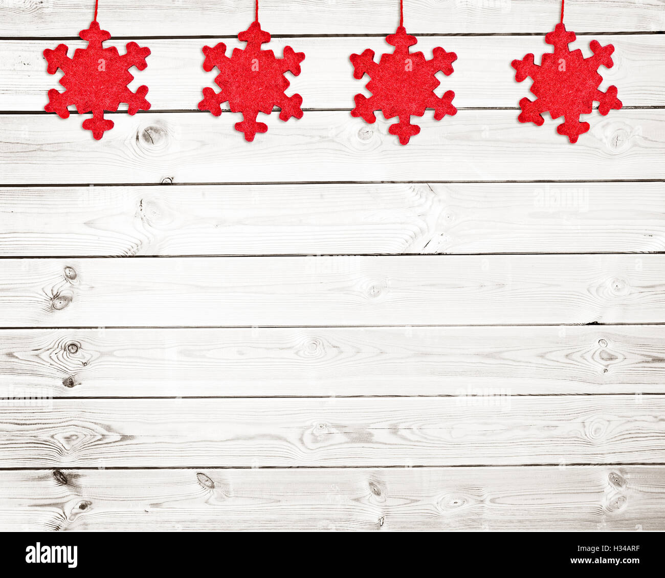 Red fabric Christmas ornaments on white wooden planks background - Stock Image