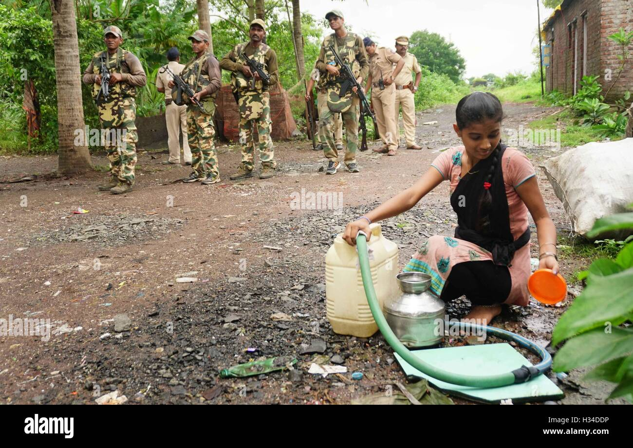 woman collects ground water Force One commandos conduct a search combing operation slum area of Uran about 47 km - Stock Image