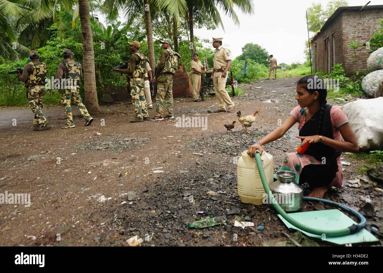 woman collects ground water Force One commandos conduct search combing operation slum area of Uran 47 km East of - Stock Image