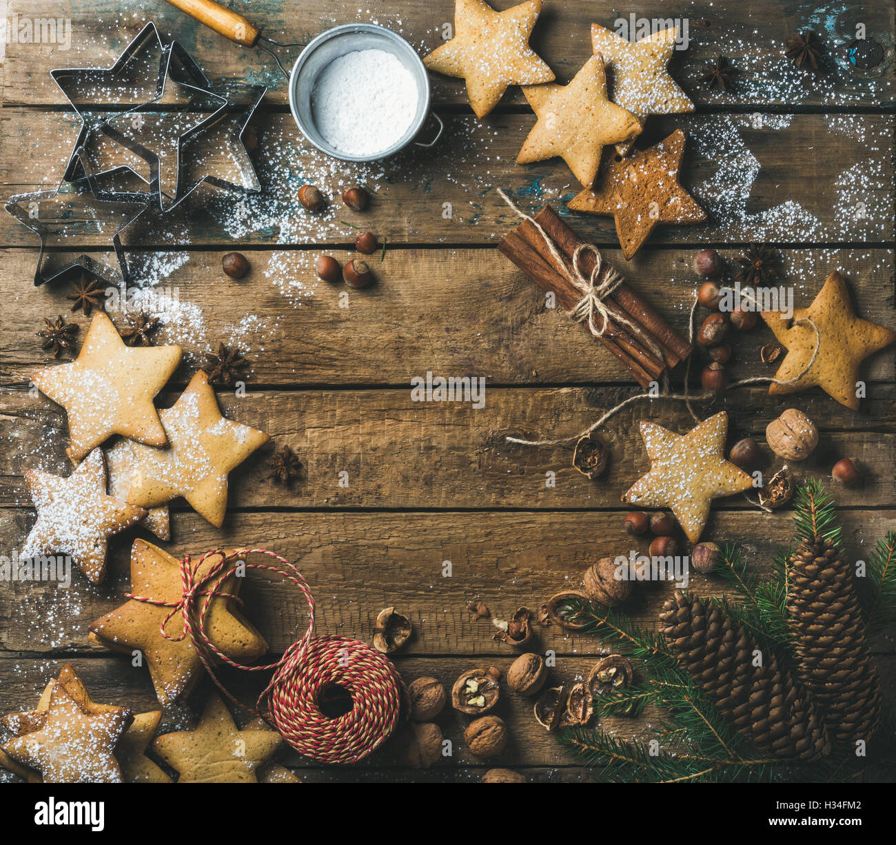 Gingerbread cookies with sugar powder, nuts, spices, fir branch, cones - Stock Image