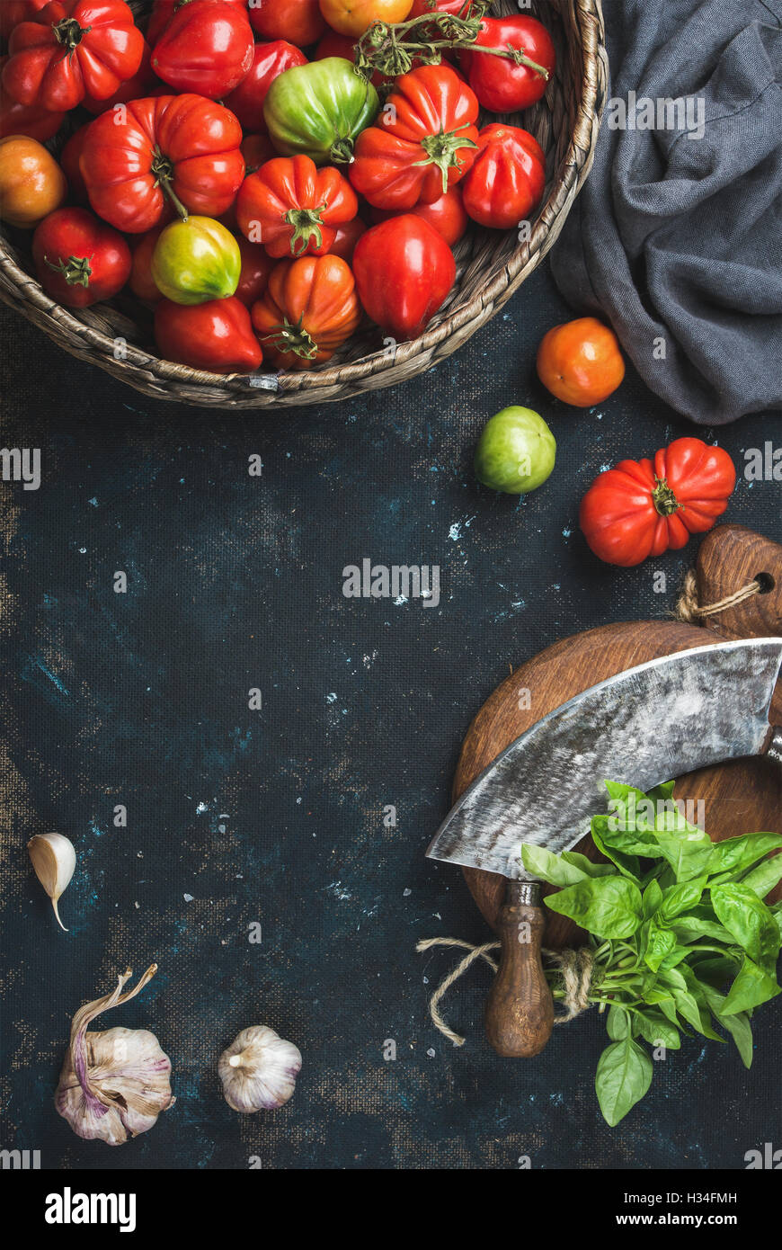 Fresh colorful ripe heirloom tomatoes in basket, copy space - Stock Image