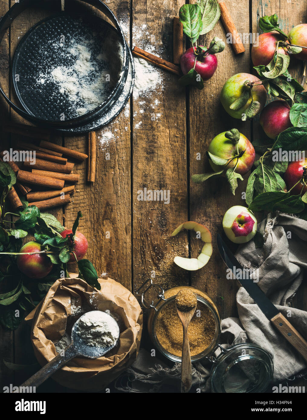 Ingredients for cooking apple pie over rustic wooden background - Stock Image