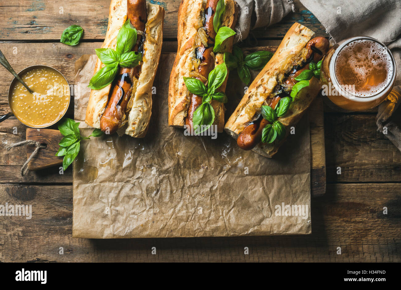 Glasses of wheat unfiltered beer and homemade grilled sausage dogs - Stock Image