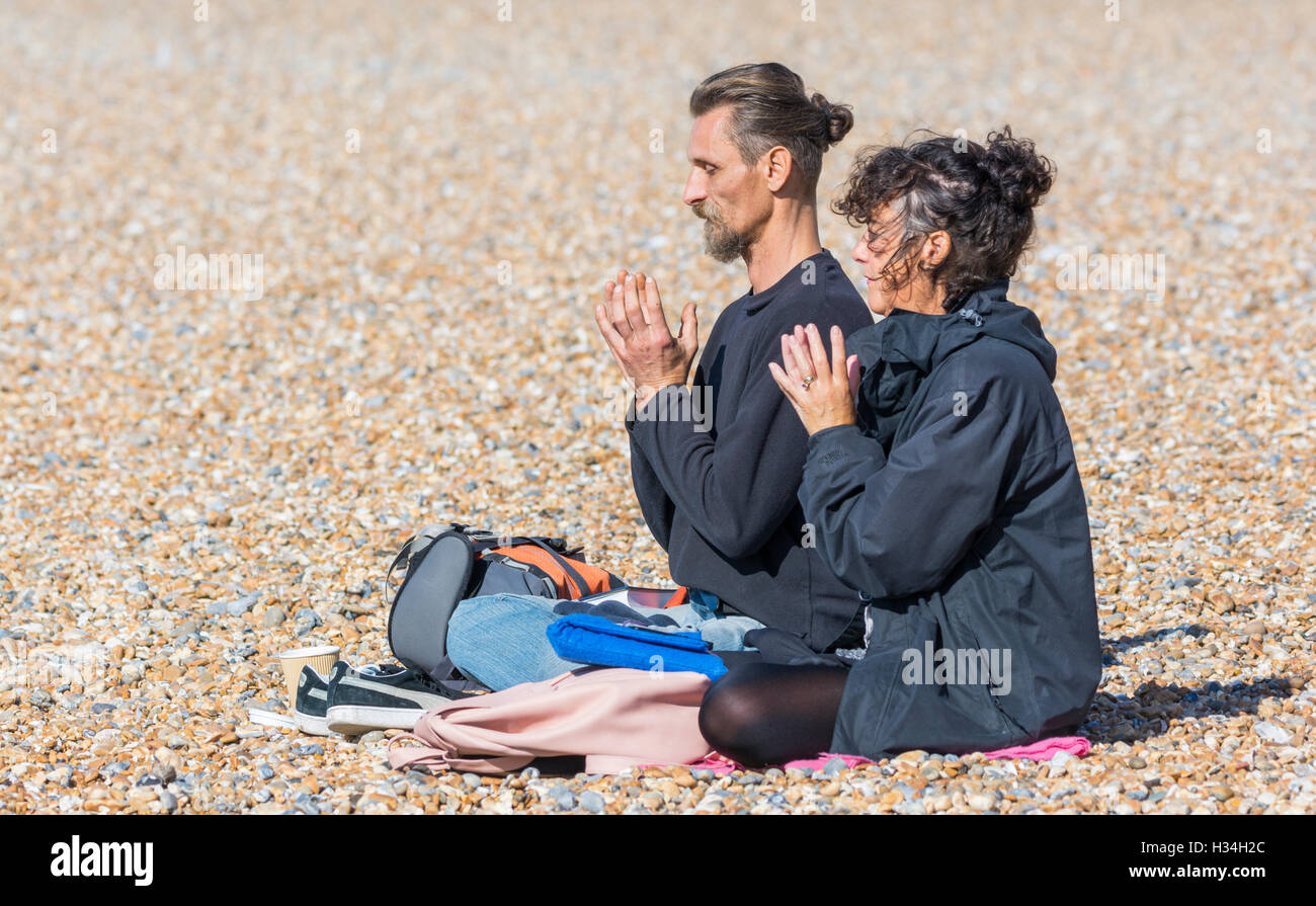 Couple sitting on a beach meditating in a praying lotus position. - Stock Image
