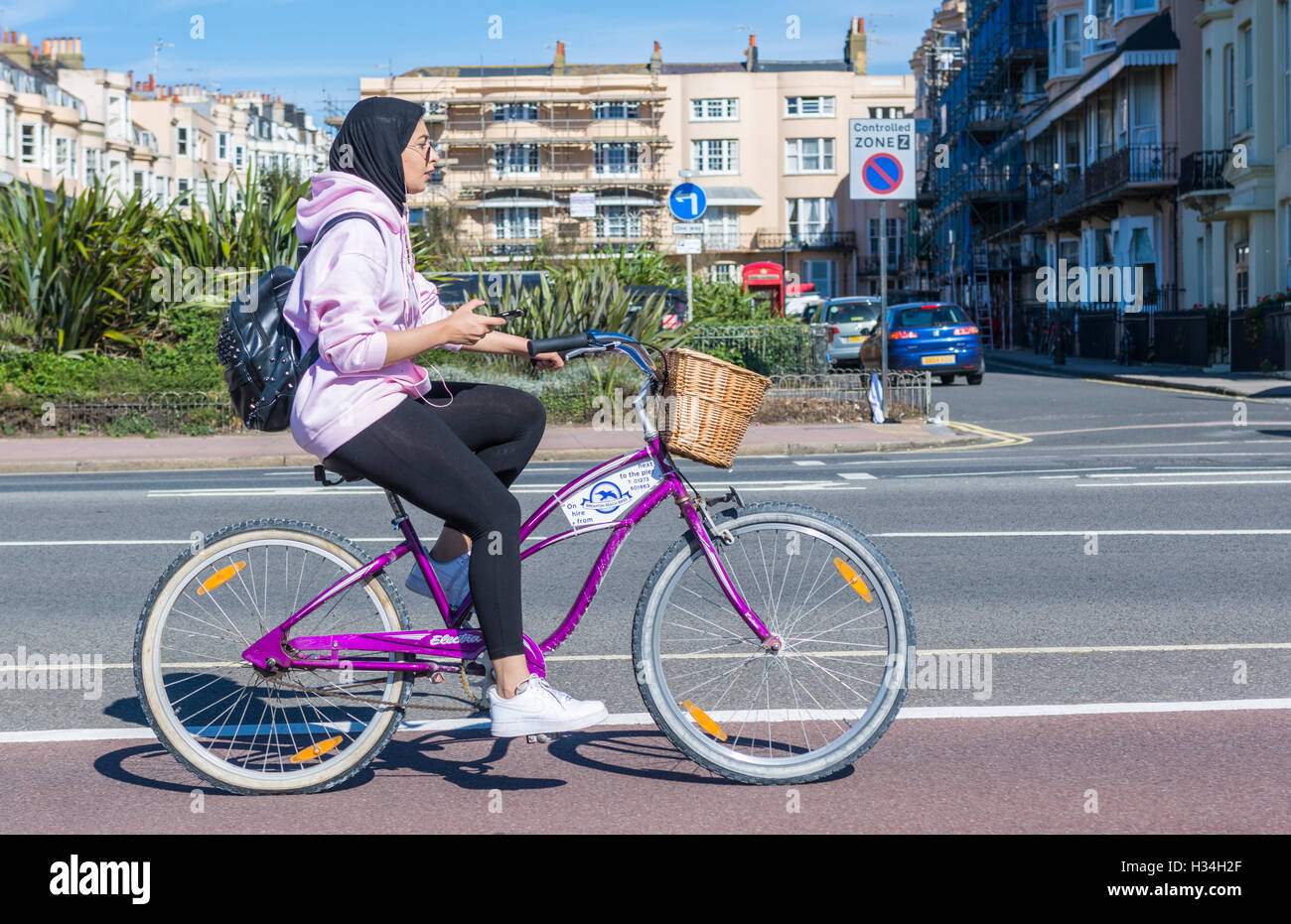 Cyclist riding on a rented bicycle from Brighton Beach Bikes in Brighton, East Sussex, England, UK. - Stock Image
