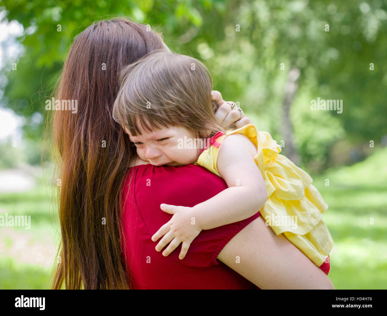 Mother holding crying baby girl with tears - Stock Image