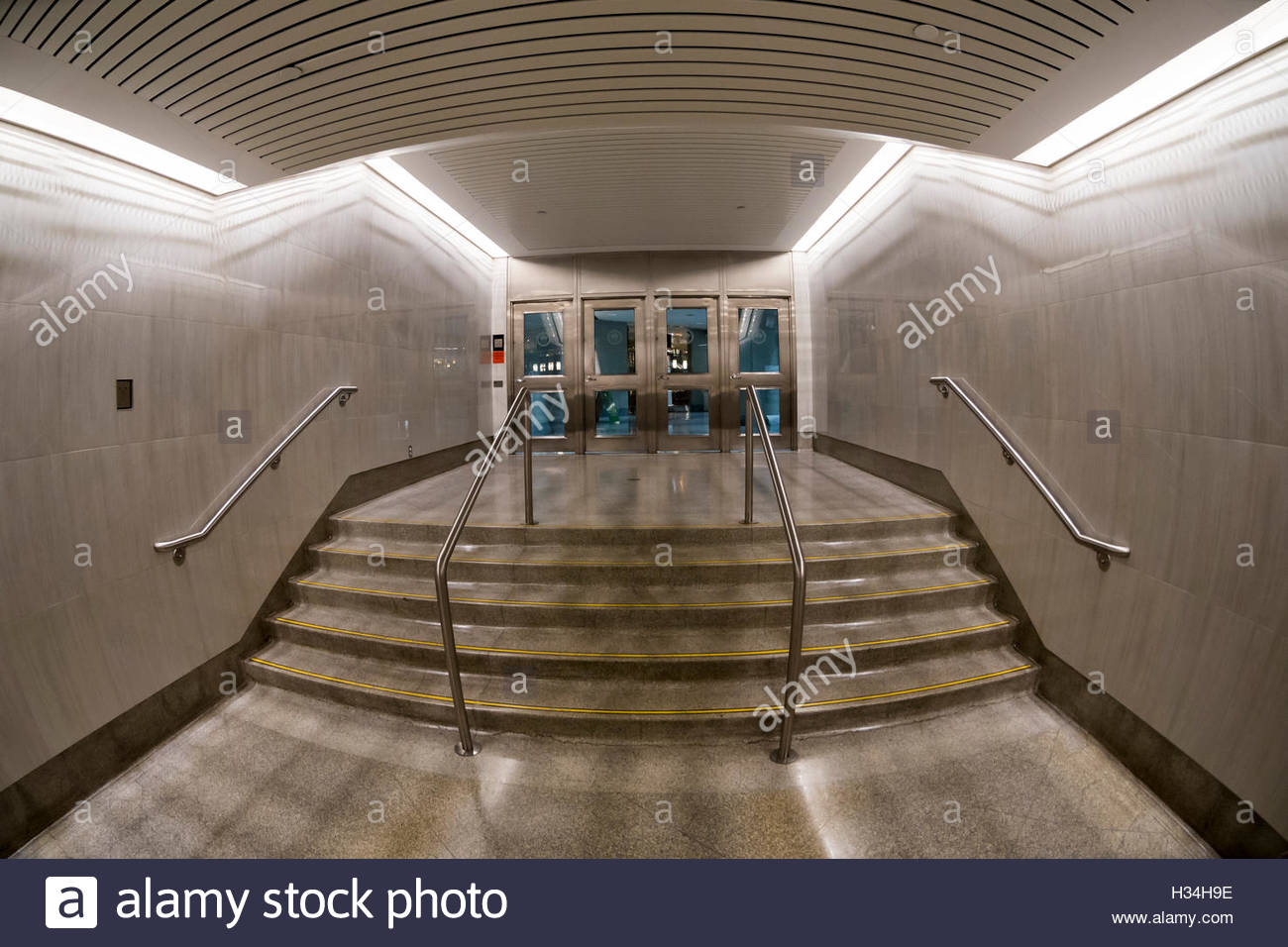 Flight of stairs in subway station. Wide lens view of a flight of stars leading to an entrance with doors. - Stock Image