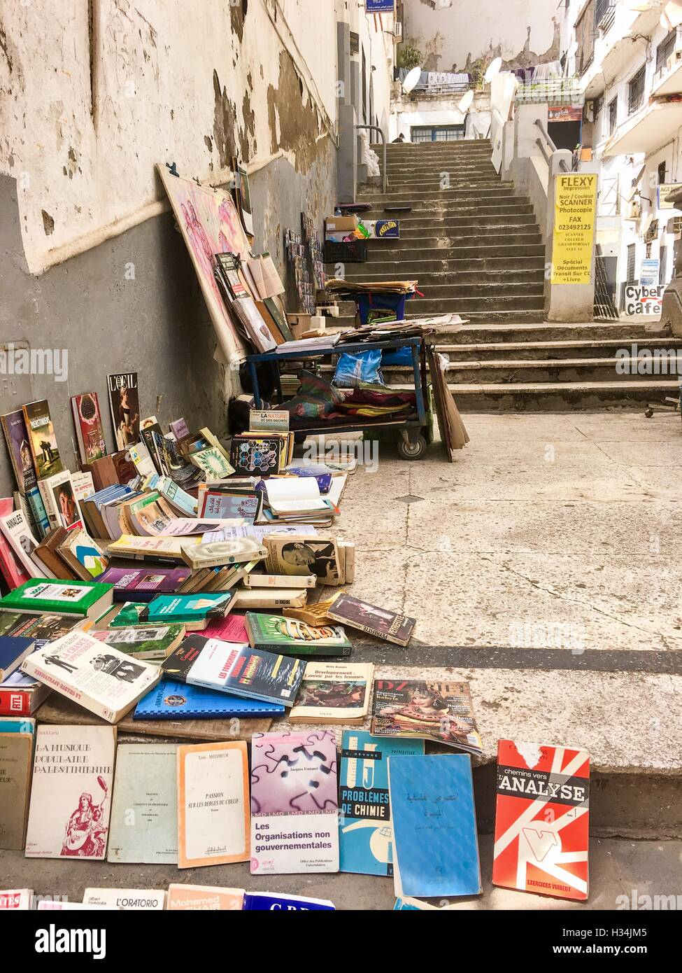 Used book seller lay out the books on the street in historical old Algiers city center. People communicating by - Stock Image