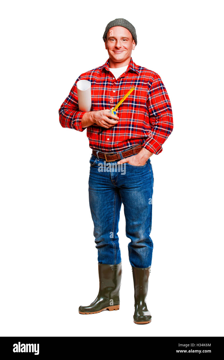 The builder in a cap with a meter and plans - Stock Image