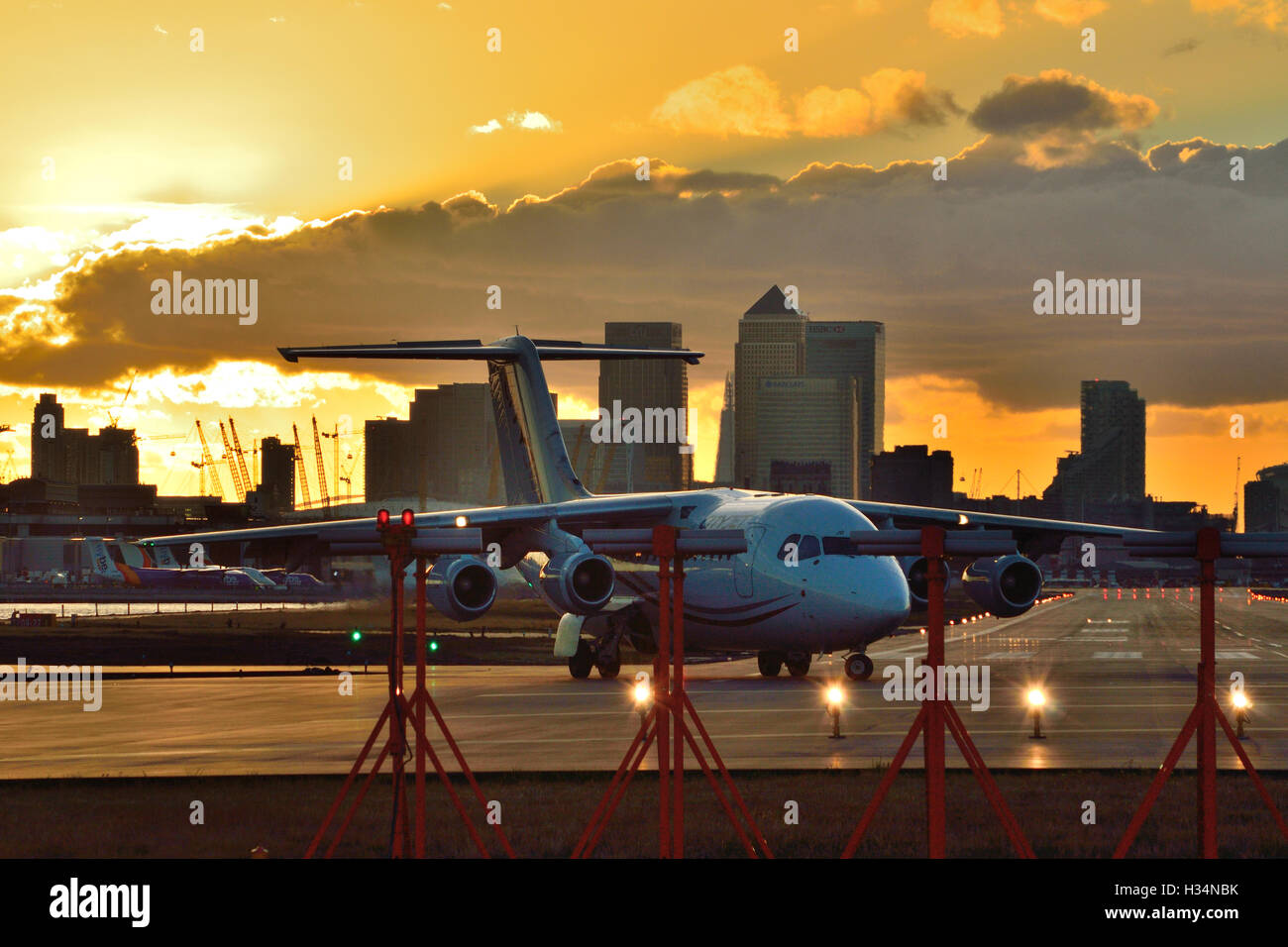 A CityJet RJ85 lines up ready to depart London City Airport as the sun sets. - Stock Image