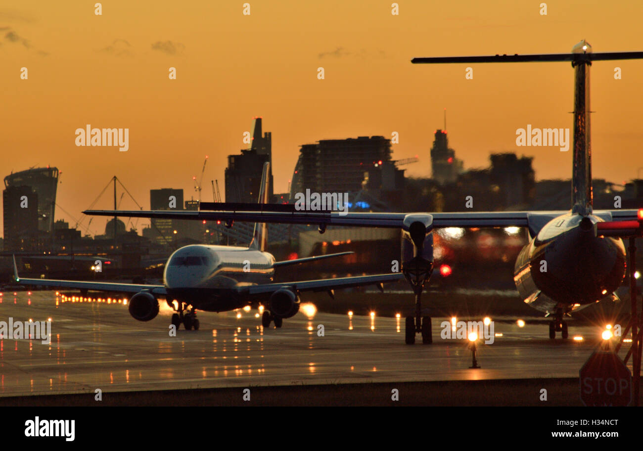 BA CityFlyer back-tracks whilst FlyBe Dash 8 waits to take off from London City Airport as the sun sets - Stock Image