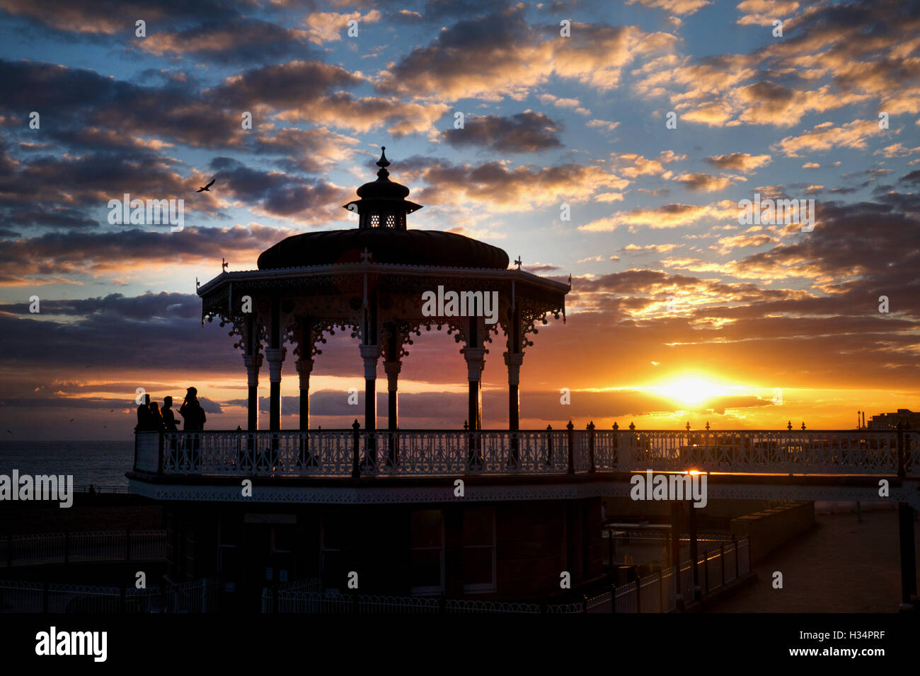 4 people on a beautiful bandstand the people are silhouetted by a yellow setting sun, and the blue and red sky. - Stock Image