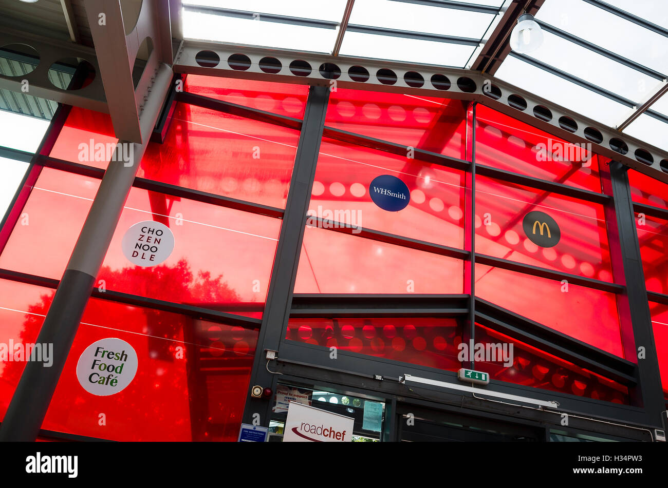 Red glass panels make a striking feature above the entrance to a Roadchef service station - Stock Image