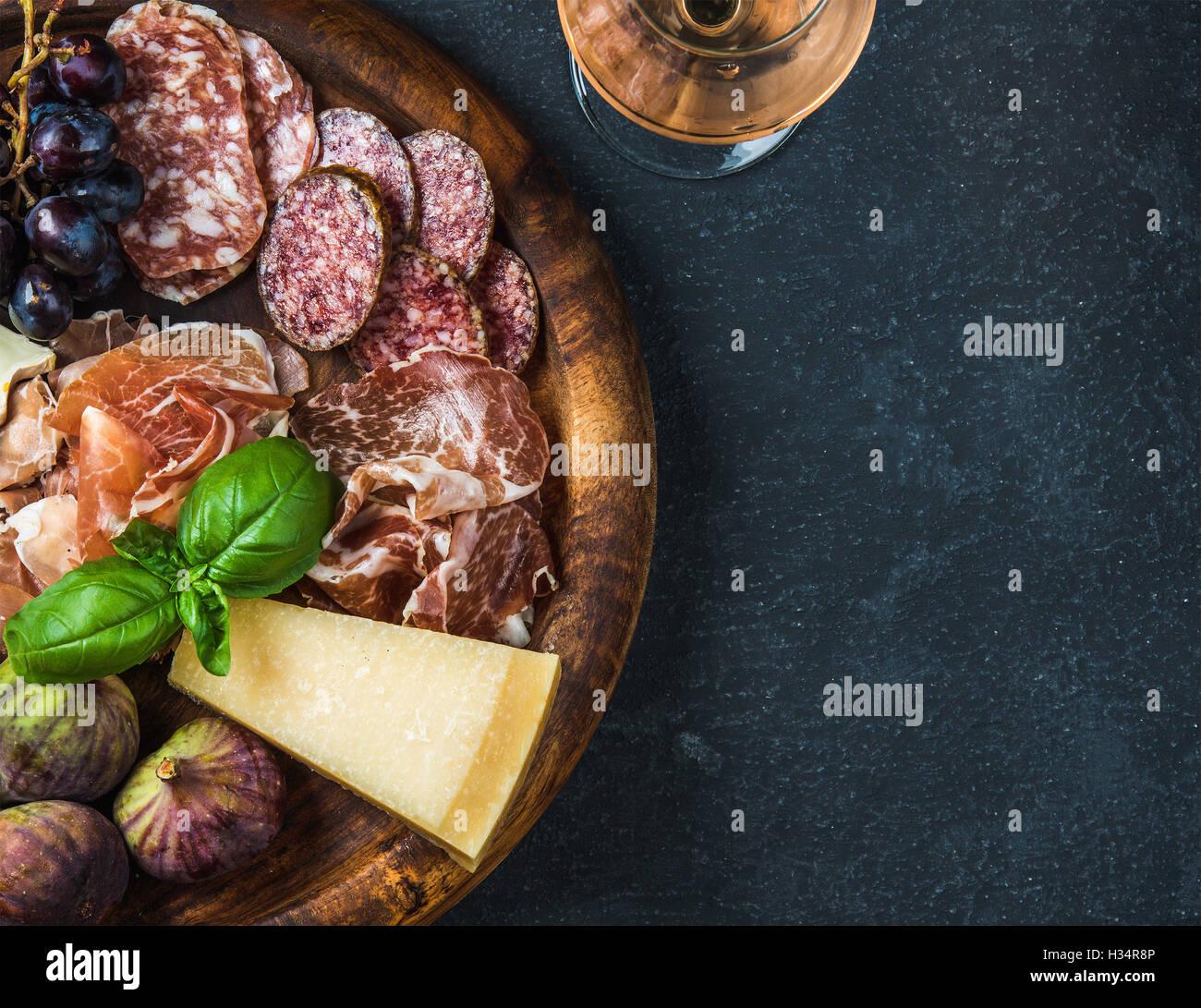 Italian antipasti snack for wine on wooden tray, dark background - Stock Image