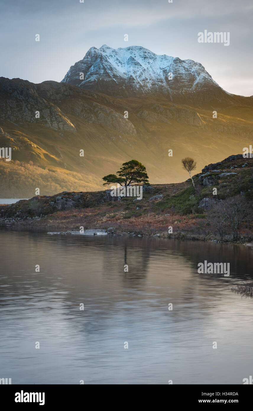 Burst of early morning sunlight on snow capped Slioch, reflected in Loch Maree, Scottish Highlands, Scotland - Stock Image