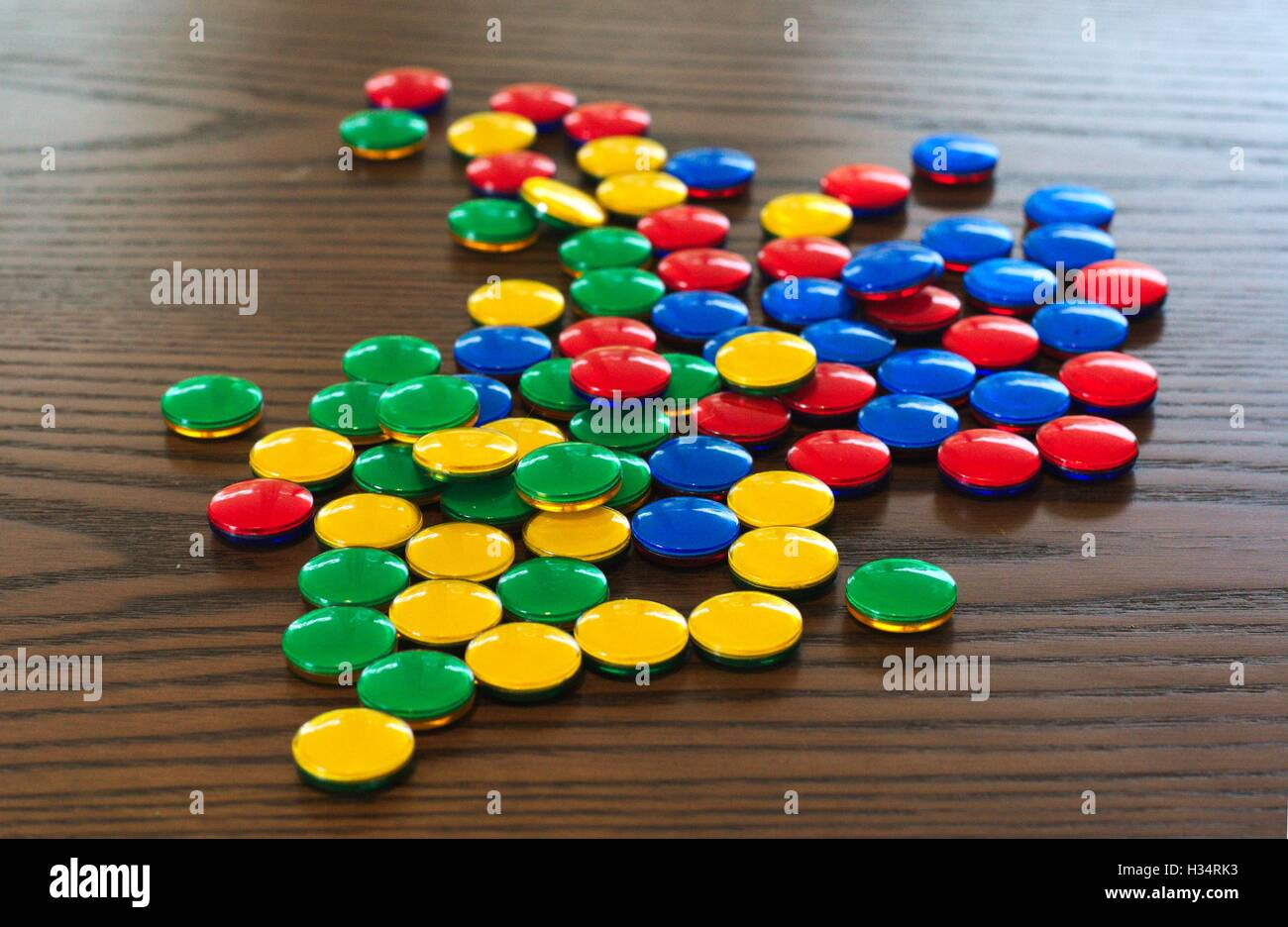 Brightly colored game counters scattered across a fake wood table top. - Stock Image