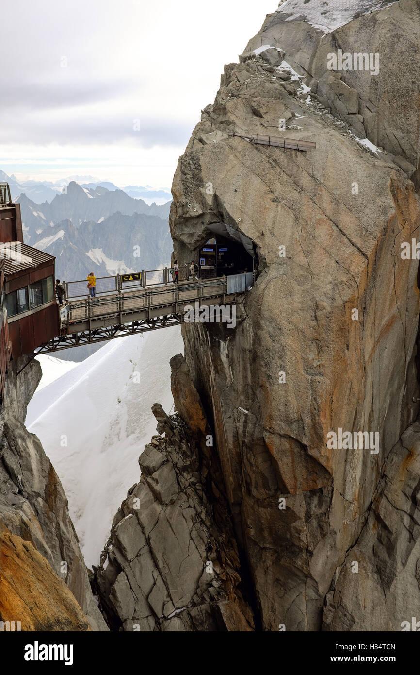 Tourists walk along the bridge that connects the peaks of Aiguille du Midi near Chamonix, France. - Stock Image