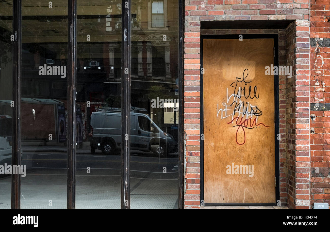 View of a vacant shop / store with boarded up door, with graffiti on it saying 'I will miss you' - Stock Image