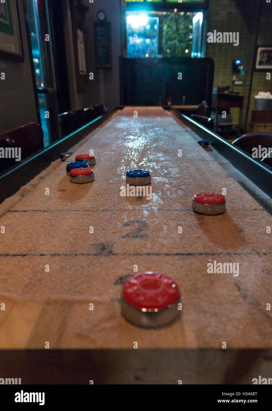 Shuffleboard Bar Game Table With Weights In Play In Dimly Lit Bar In The  USA