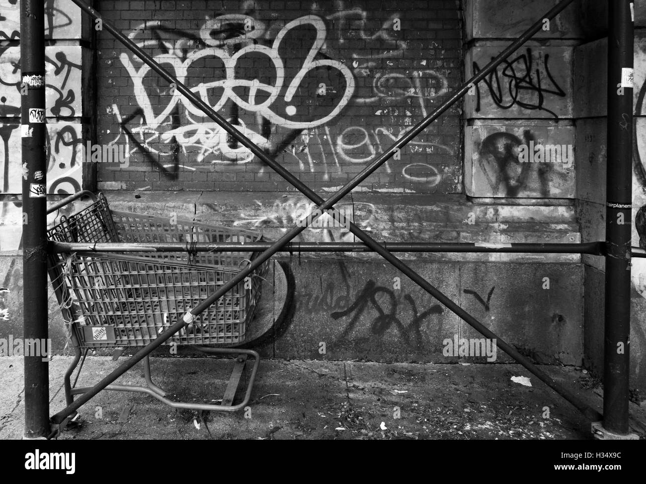 Monochrome gritty image of scaffolding crossed poles with abandoned shopping trolley and a graffiti covered wall - Stock Image