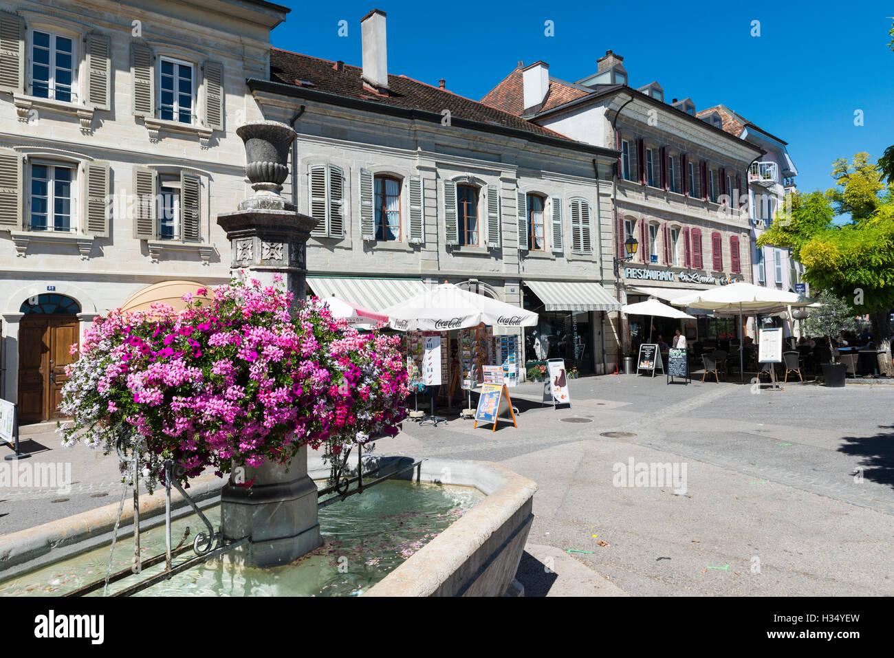 Fountain with flowers, Rue de Rive, Nyon, canton Vaud, Switzerland - Stock Image