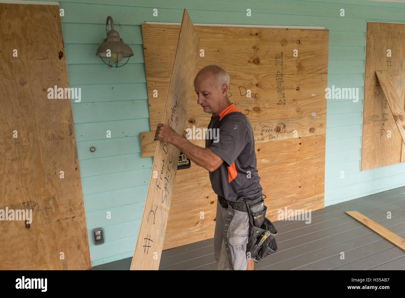 Sullivan's Island, South Carolina, USA. 5th October, 2016. Workers board up a home along the beach front in - Stock Image