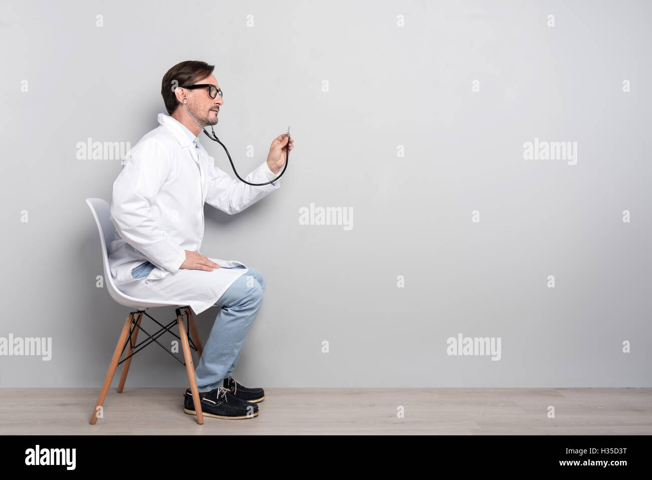 Handsome doctor diagnosing the patient - Stock Image