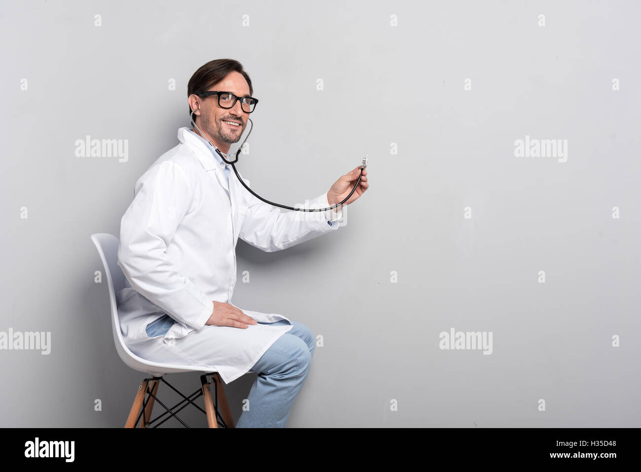 Young doctor with stethoscope on a grey background - Stock Image