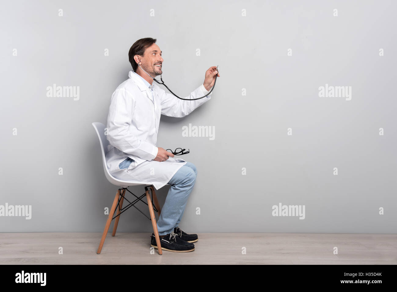 Happy doctor with stethoscope doing his work - Stock Image