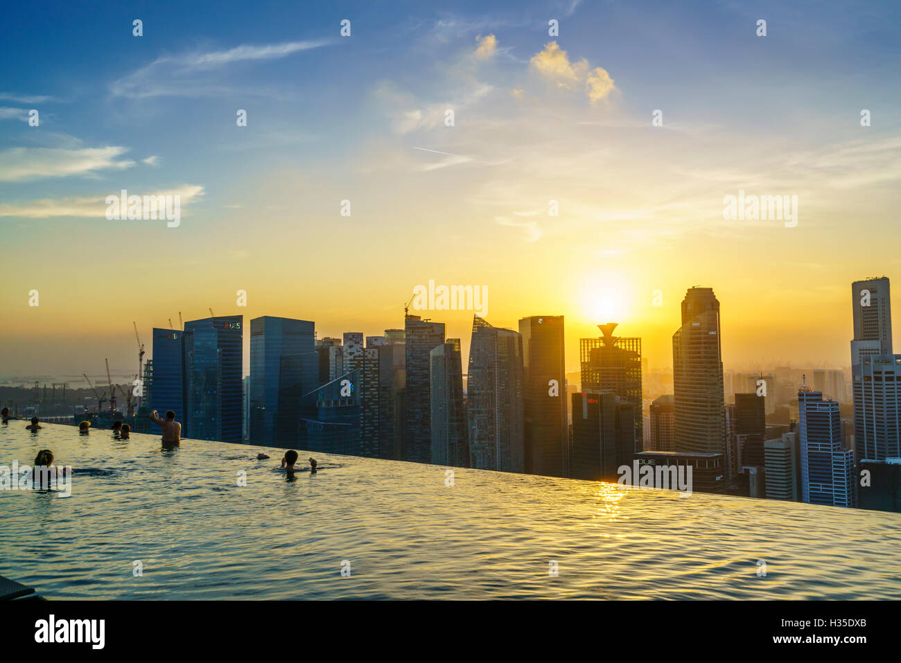Infinity pool on the roof of the Marina Bay Sands Hotel with spectacular views over the Singapore skyline at sunset, - Stock Image