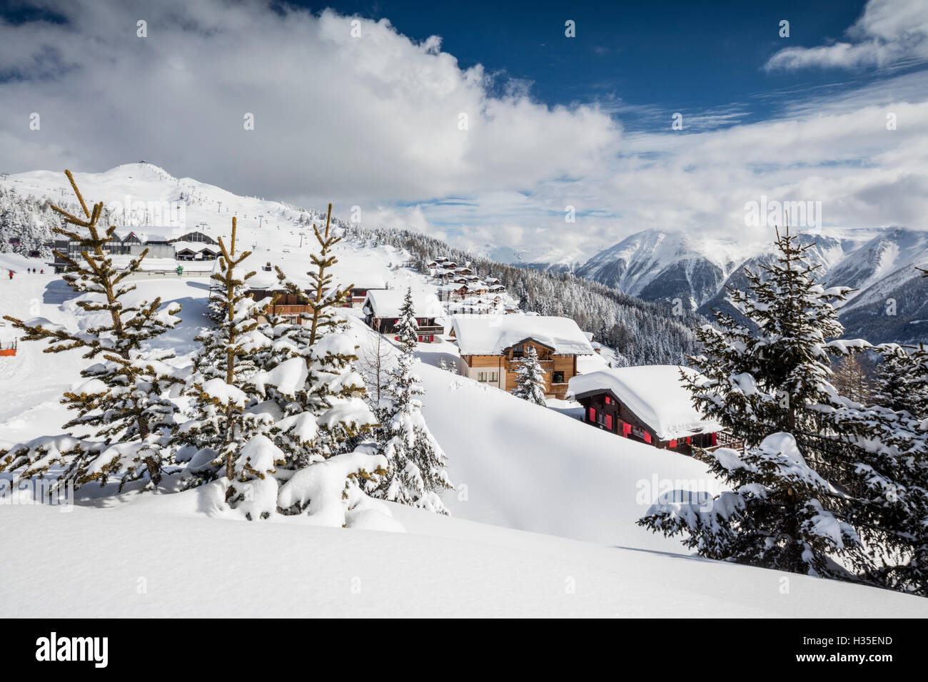 The winter sun shines on the snowy mountain huts and woods, Bettmeralp, district of Raron, canton of Valais, Switzerland - Stock Image