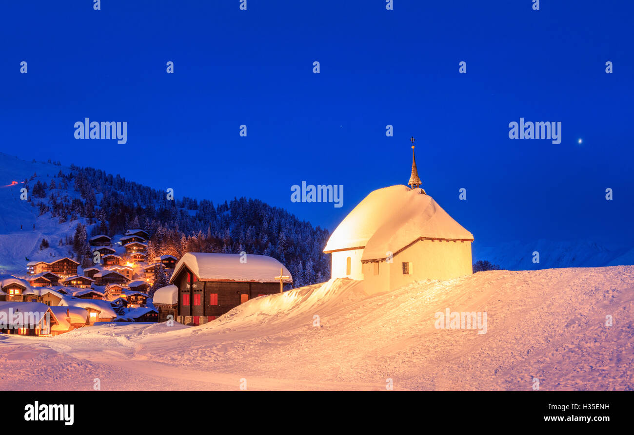 Blue dusk on the alpine village and church covered with snow, Bettmeralp, district of Raron, canton of Valais, Switzerland Stock Photo