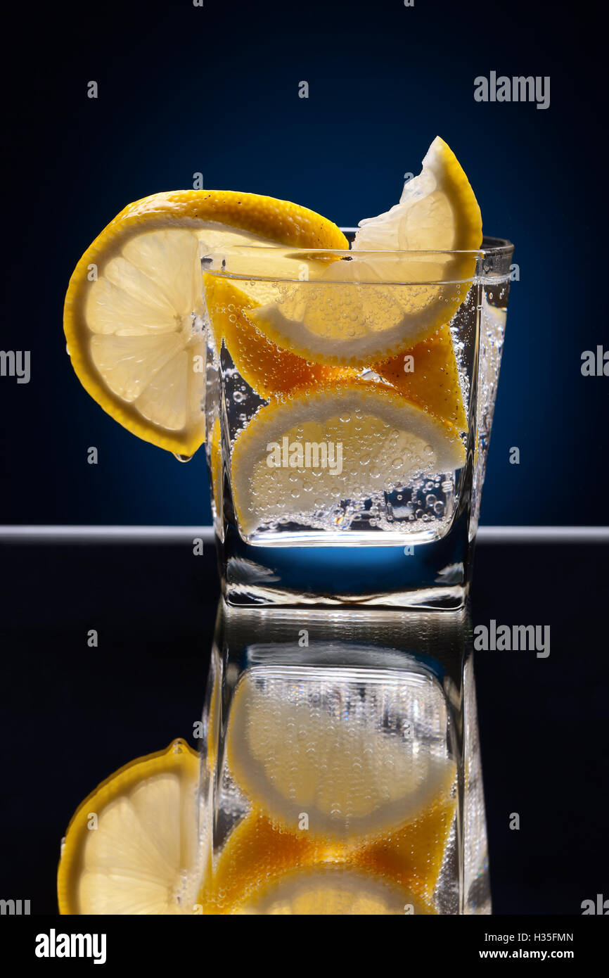 Glass of alcoholic drink with lemon on a reflective background Stock Photo