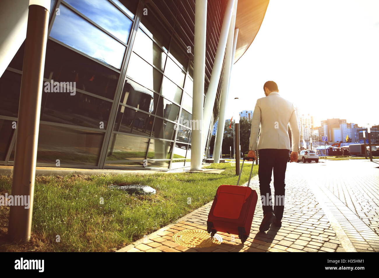 Rear view of young Businessman walking down street with luggage - Stock Image