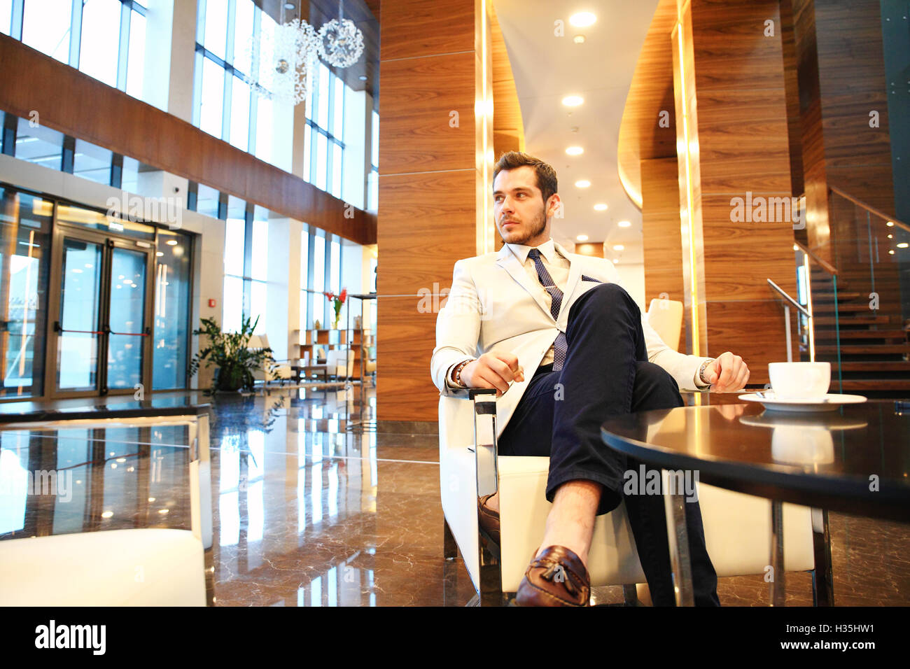 happy young businessman sitting on sofa in hotel lobby - Stock Image