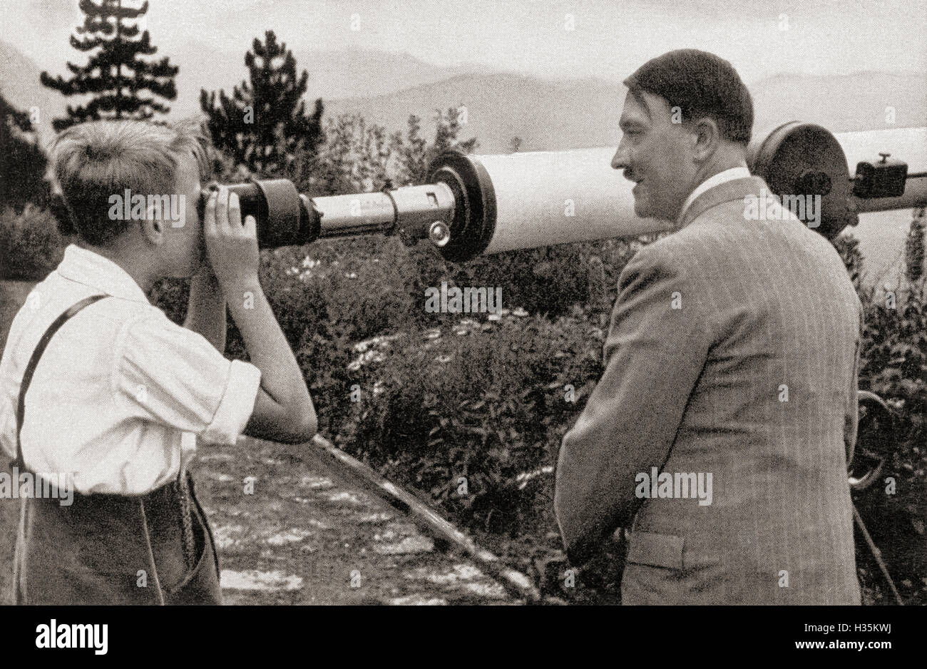 Adolf Hitler at his residence in Obersalzberg, Bavaria, Germany in 1936, watching a boy observing the Unterberg - Stock Image