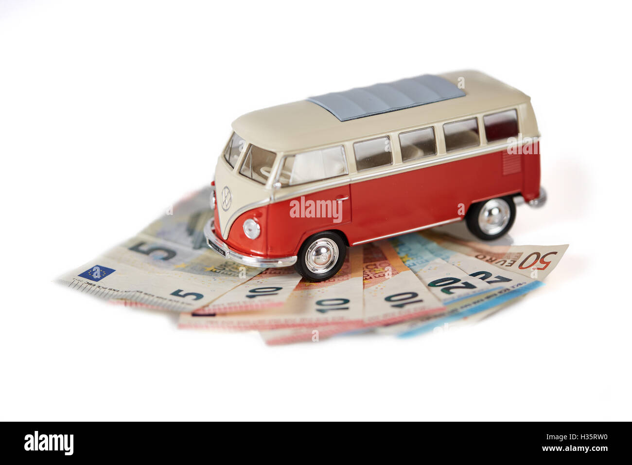 Isolated figurine vw bus on european banknotes money - Stock Image