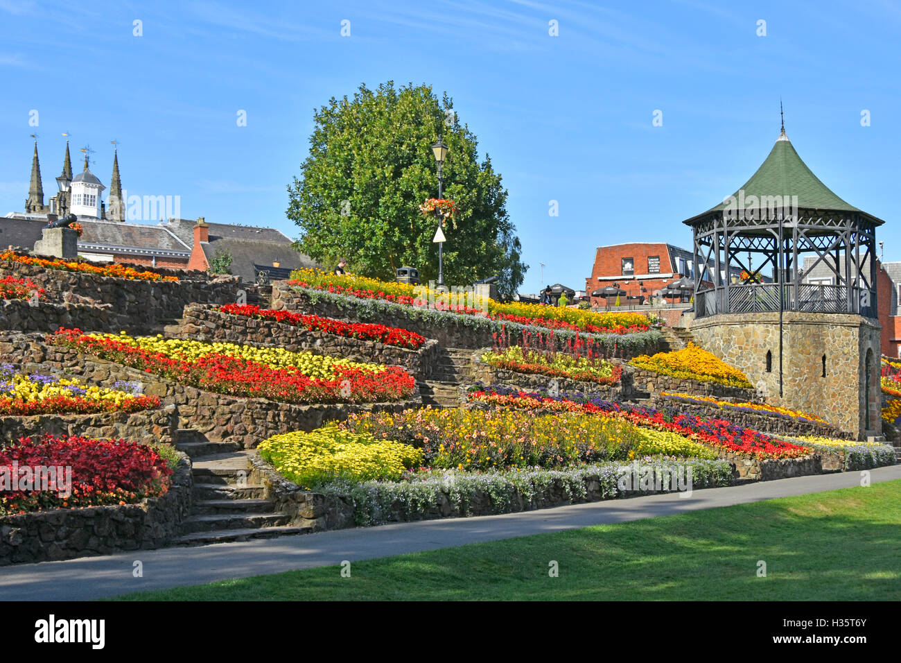 Summer flowers display on terraced embankment in public park gardens beside bandstand in Castle Grounds, Tamworth, - Stock Image