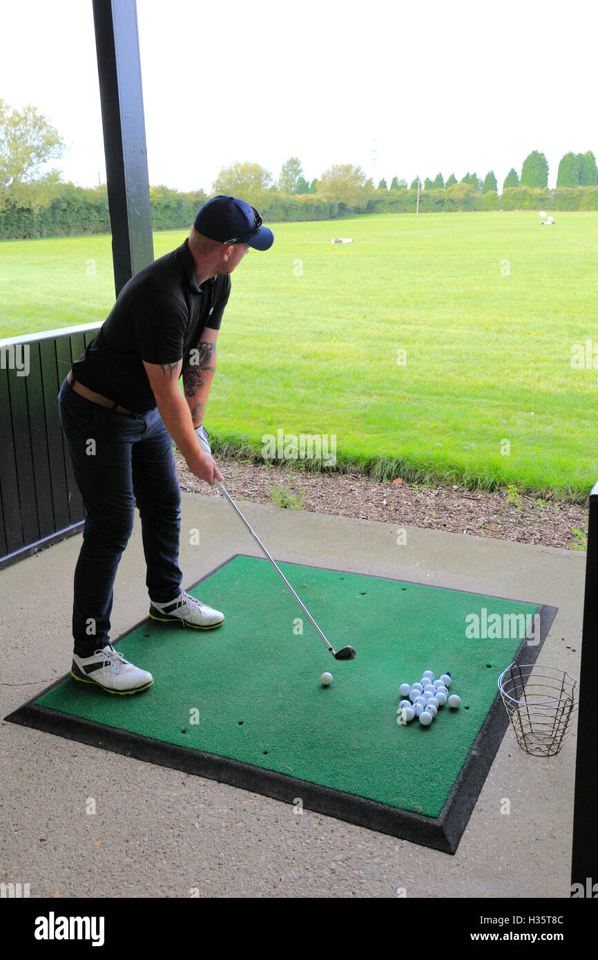 Golfer drives from a driving range, golf course, Cambridgeshire - Stock Image