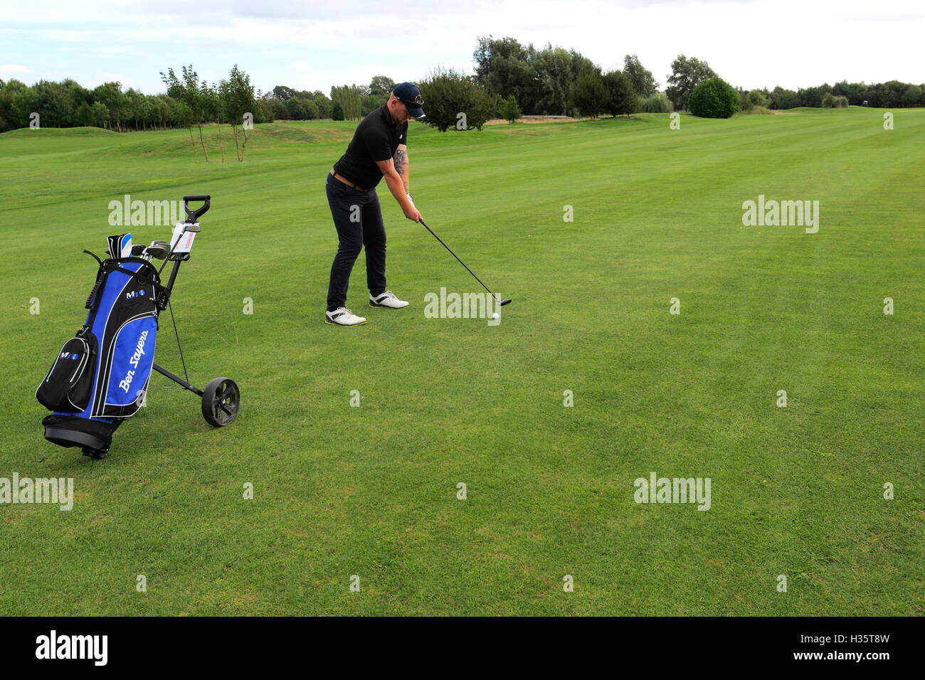 golfer drives from the tee on a rural golf course, Cambridgeshire - Stock Image